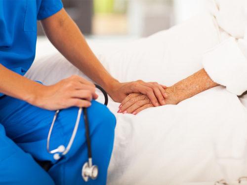 Nurse holding an elderly woman's hand