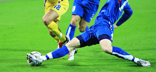 Man kicking a soccer ball in a game